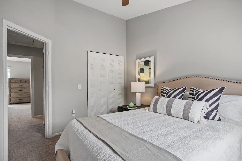 Model home's primary bedroom with plush carpeting at The Coast of Naples Florida in Naples, Florida