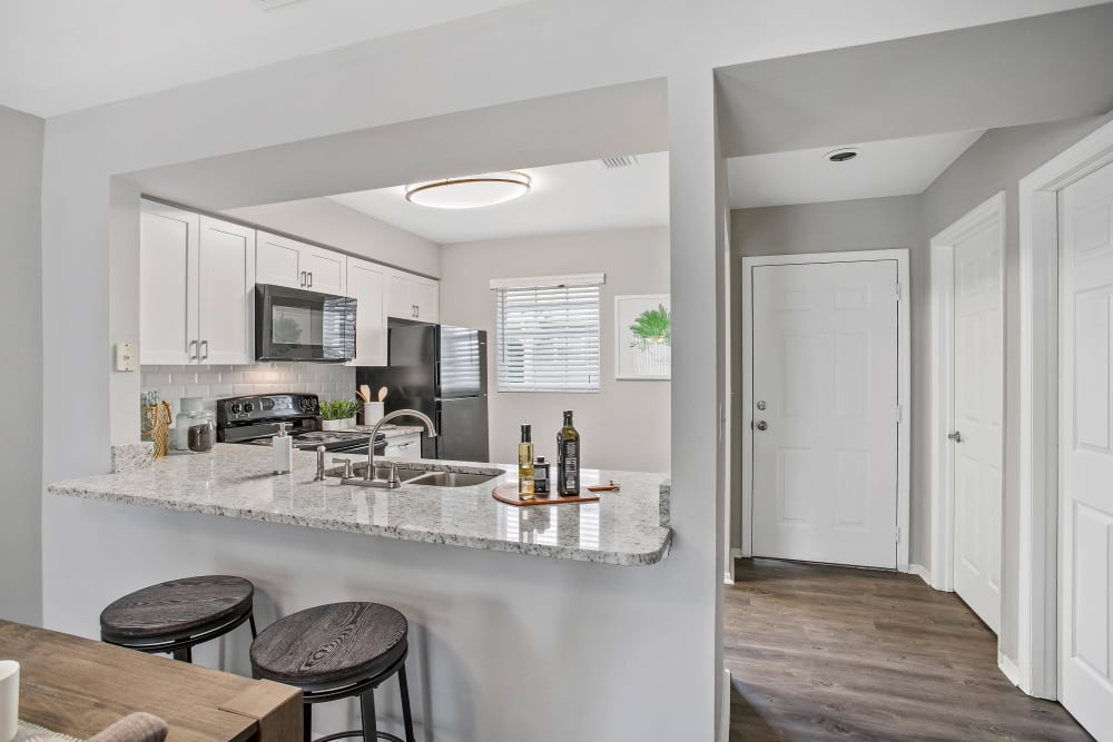 Hardwood flooring and granite countertops in a model townhome's kitchen at The Coast of Naples Florida in Naples, Florida