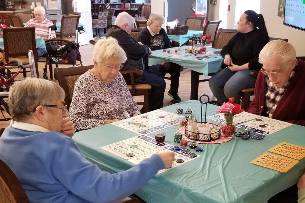 3 Residents sitting at a table in a large room playing bingo at Emery Place in Robins, Iowa