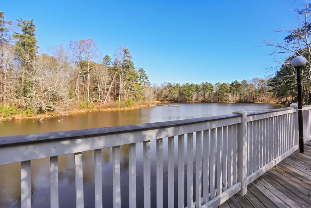 View of the lake surrounded by mature trees from the lakeside boardwalk at Reserve at Peachtree Corners in Norcross, Georgia