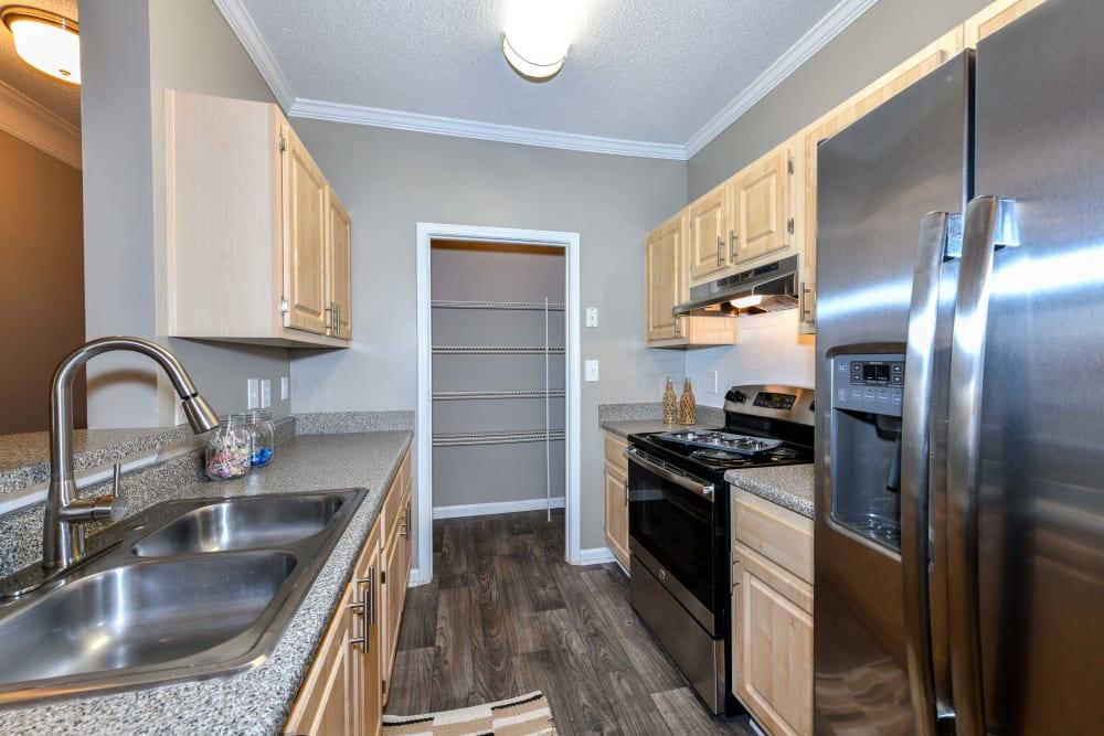 Beautiful hardwood flooring and granite countertops in a model home's kitchen at 860 South in Stockbridge, Georgia