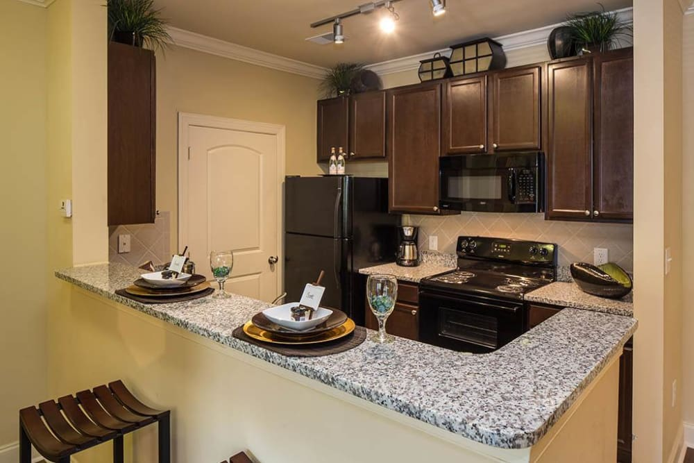 Modern kitchen with granite countertops and a breakfast bar in a model home at The Preserve at Greison Trail in Newnan, Georgia