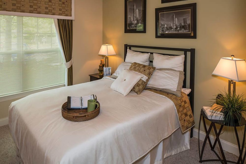 Well-furnished primary bedroom with plush carpeting in a model apartment at The Preserve at Greison Trail in Newnan, Georgia