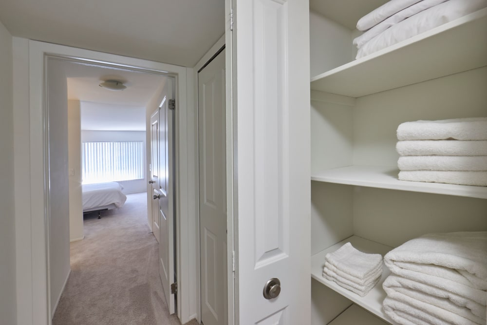 Hallway closet with linens and a view of bedroom at Lakeside Terraces in Sterling Heights, Michigan