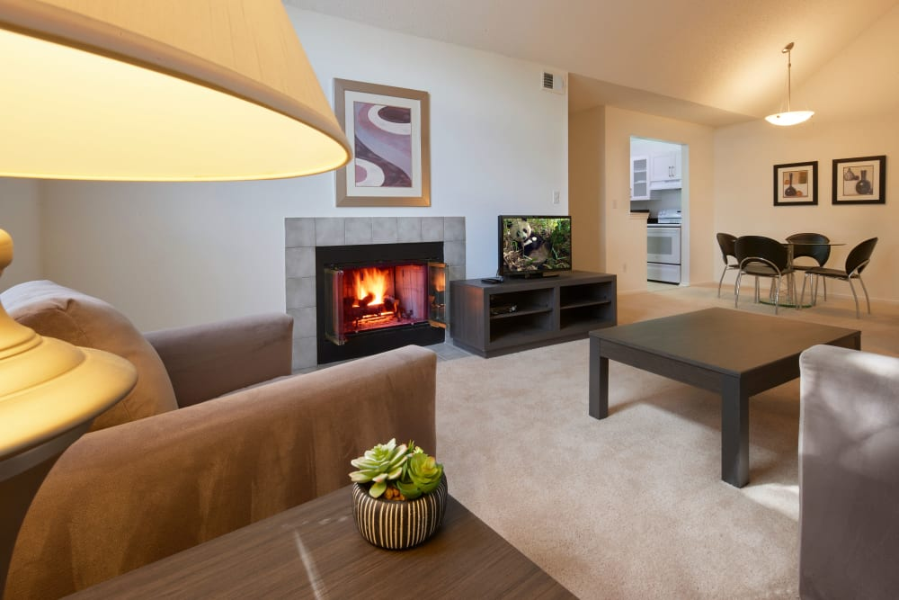 Well decorated model living room with fireplace at Briar Cove Terrace Apartments in Ann Arbor, Michigan