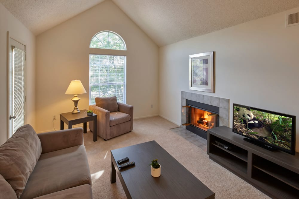 Well lit model living room with fireplace at Briar Cove Terrace Apartments in Ann Arbor, Michigan
