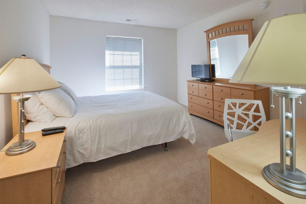 Well decorated model bedroom with vanity mirror at Briar Cove Terrace Apartments in Ann Arbor, Michigan
