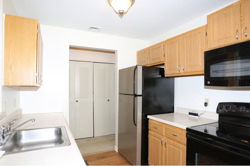 Kitchen with wood cabinets at Bennington Hills Apartments in West Henrietta, New York