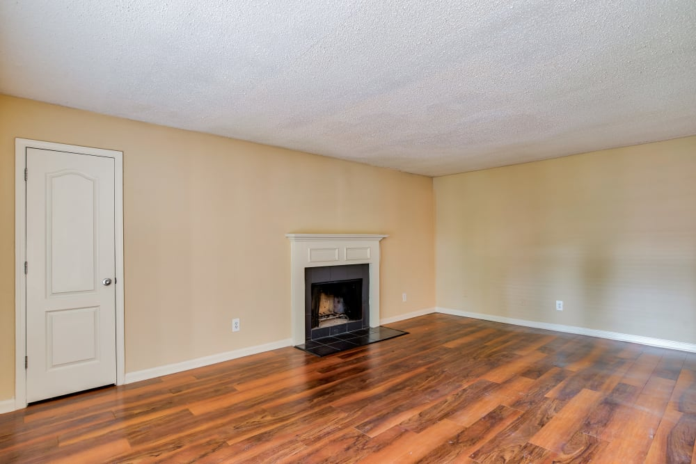 Living room with wood floors and fireplace at The Lodge on the Chattahoochee Apartments in Sandy Springs, Georgia