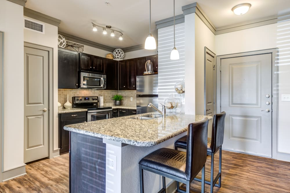 Beautiful hardwood floors and granite countertops in the kitchen at The Sovereign in Fort Worth, Texas