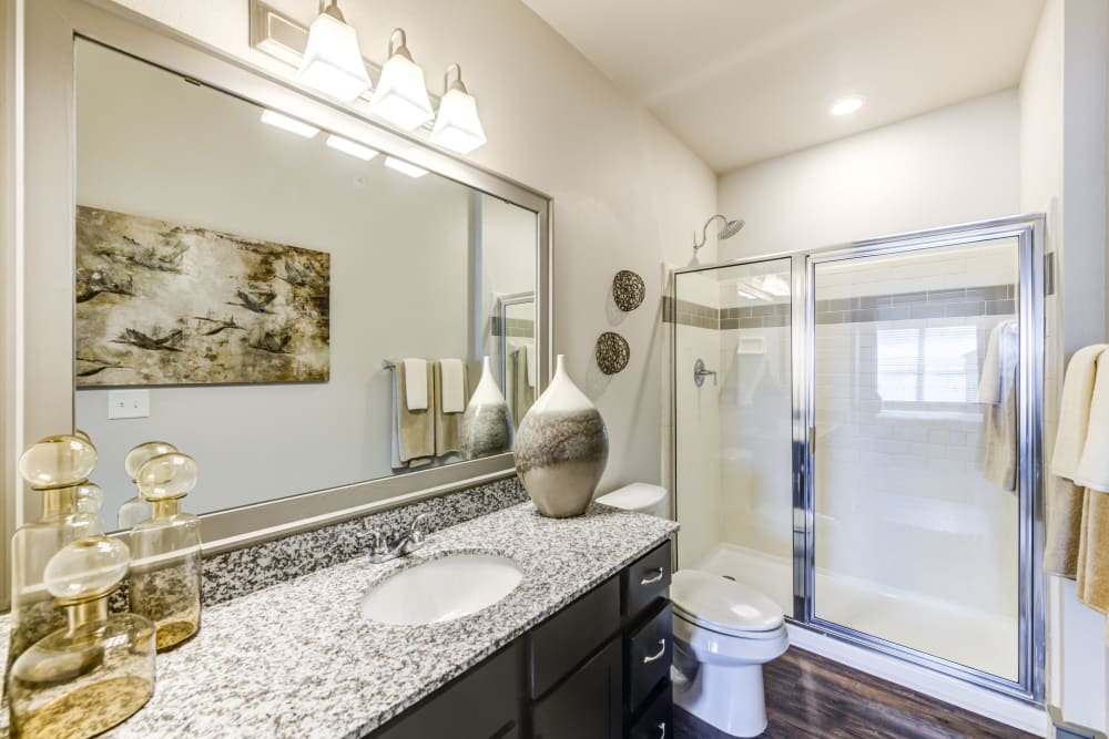 Model bathroom with granite countertops and large vanity mirror at The Sovereign in Fort Worth, Texas