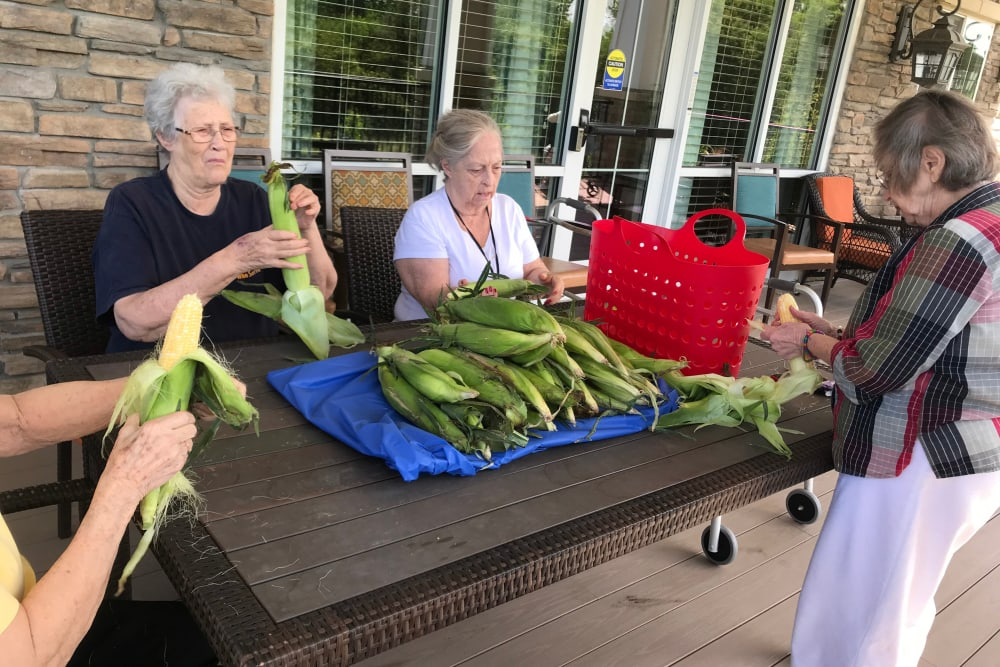 Residents shucking corn at Edencrest at Riverwoods in Des Moines, Iowa