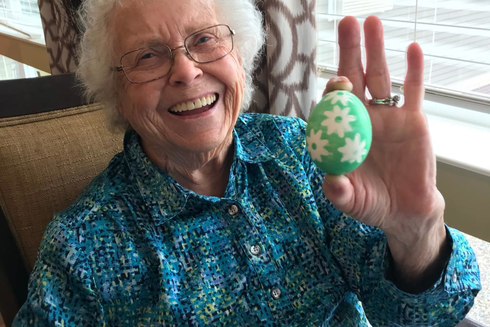 Resident smiling and showing her Easter egg at Edencrest at Riverwoods in Des Moines, Iowa