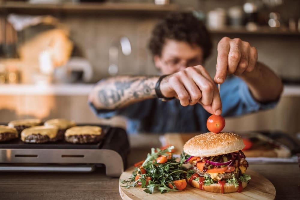 Chef making a gourmet hamburger near Carvel Harbour Pointe in Mukilteo, Washington