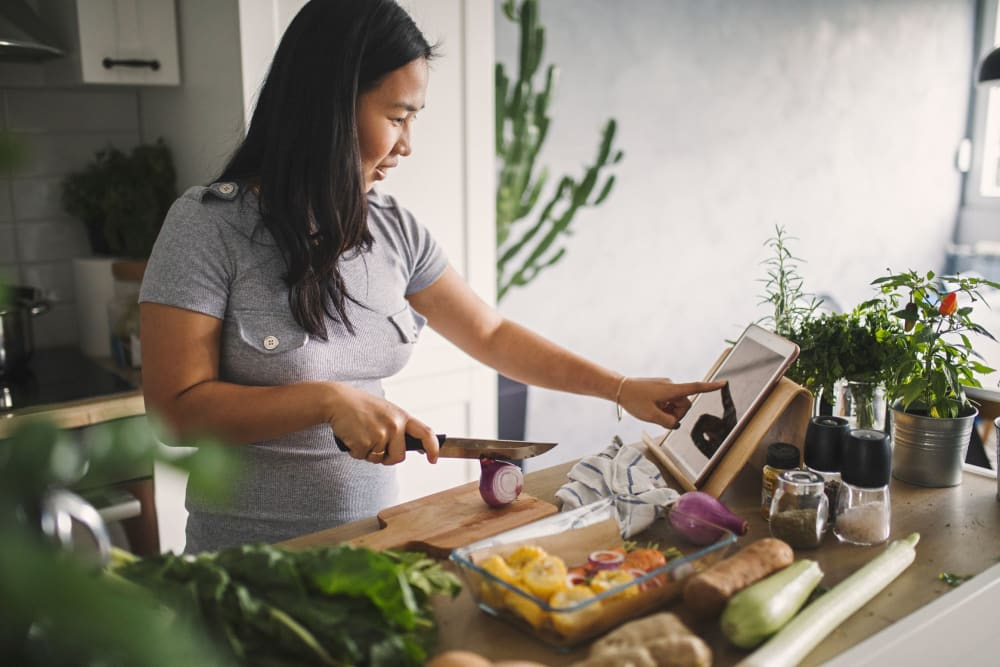 Resident cutting up vegetables for meal prep using her iPad to view recipe at Carvel Harbour Pointe in Mukilteo, Washington