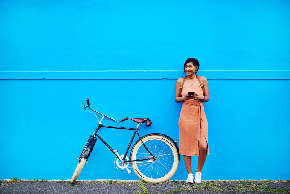 Resident relaxing against a blue wall next to bike near Carvel Harbour Pointe in Mukilteo, Washington