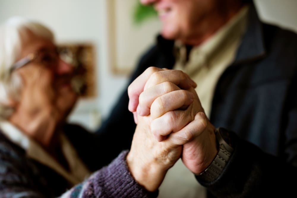 Two residents holding hands at The Meridian at Brandon in Tampa, Florida