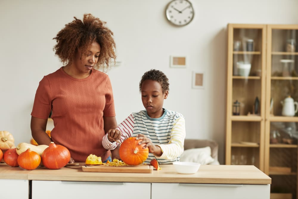 Mother and son carving pumpkins in kitchen