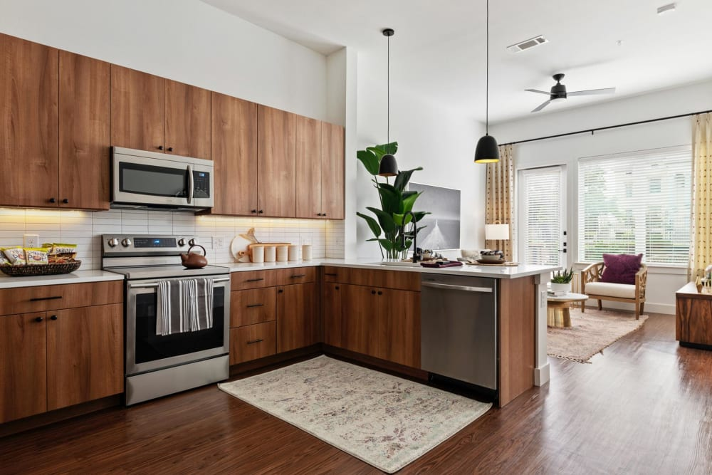 Stainless-steel appliances and custom wood cabinetry in a model home's kitchen at 4600 Ross in Dallas, Texas