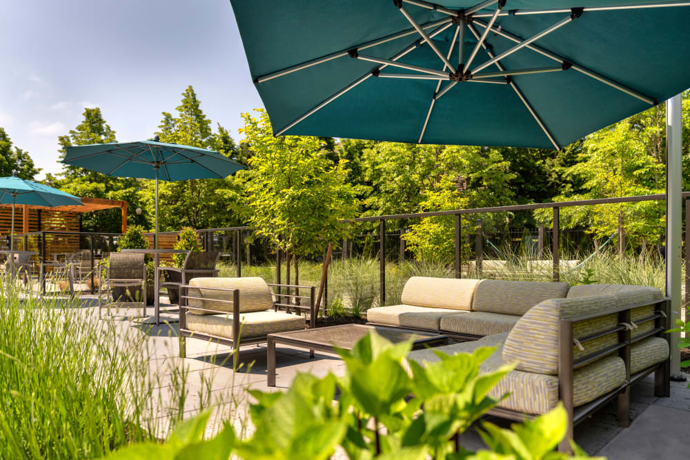 An outdoor covered seating area surrounded by lush landscaping at Brookside Village in Auburn, Washington