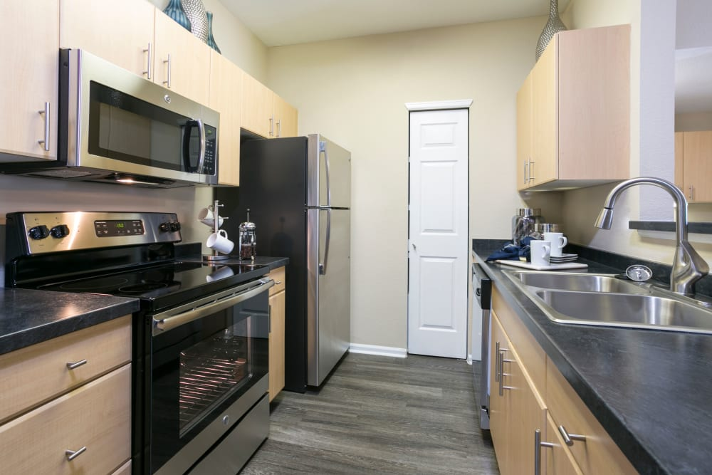 Kitchen with wood-style flooring and stainless steel appliances at Crestone Apartments in Aurora, Colorado