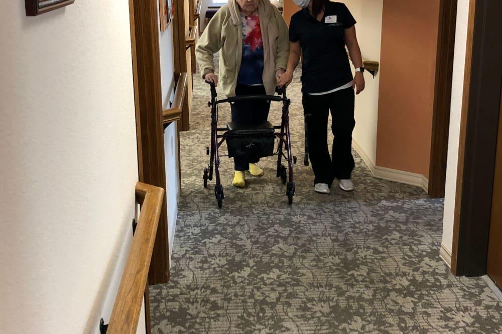 Staff provides walking assistance to resident at Landings of Sauk Rapids in Sauk Rapids, Minnesota