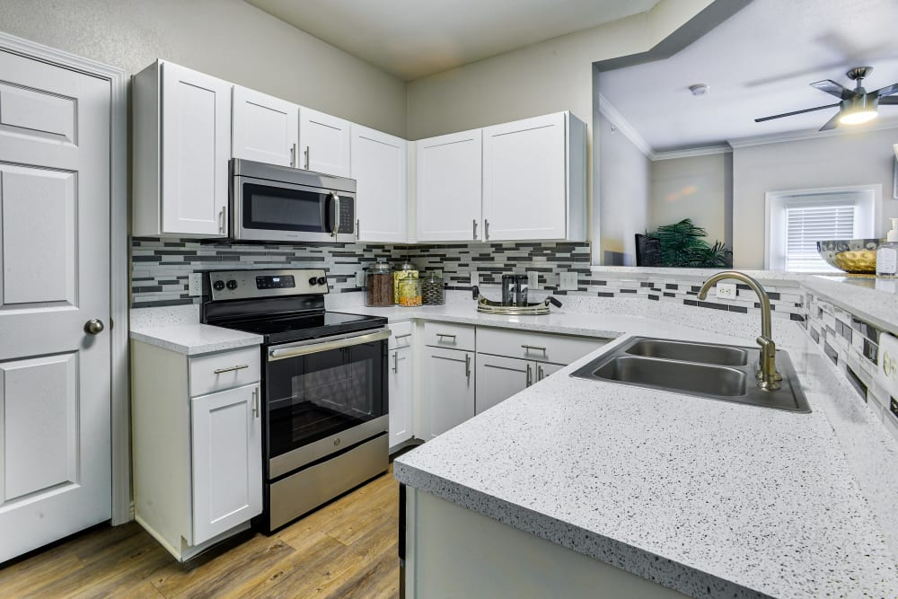 Kitchen with white cabinets and stainless-steel appliances at Bella Springs Apartments in Colorado Springs, Colorado