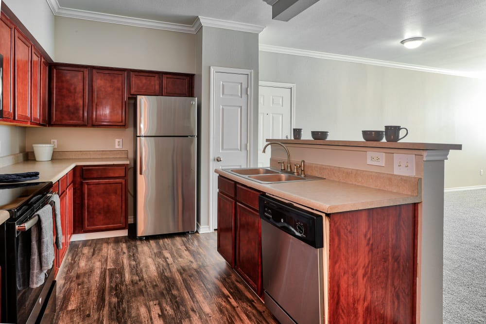 Kitchen with cherry cabinets and stainless-steel appliances at Bella Springs Apartments in Colorado Springs, Colorado