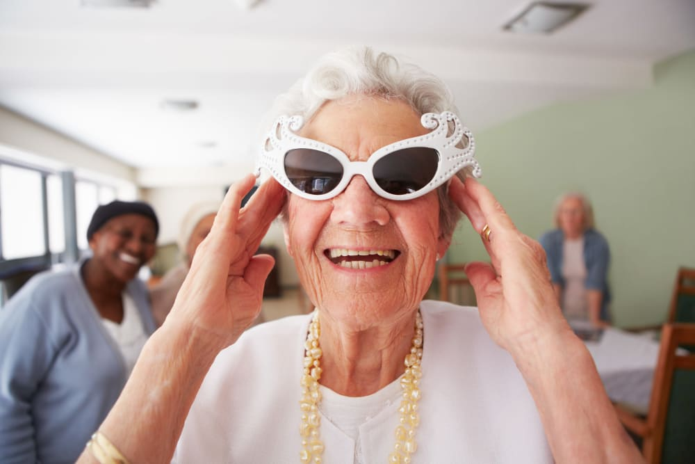 Resident smiles for the camera with stylish sunglasses at Arlington Place of Grundy Center in Grundy Center, Iowa