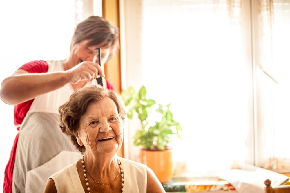 A resident enjoys getting her hair styled near at Arlington Place of Grundy Center in Grundy Center, Iowa