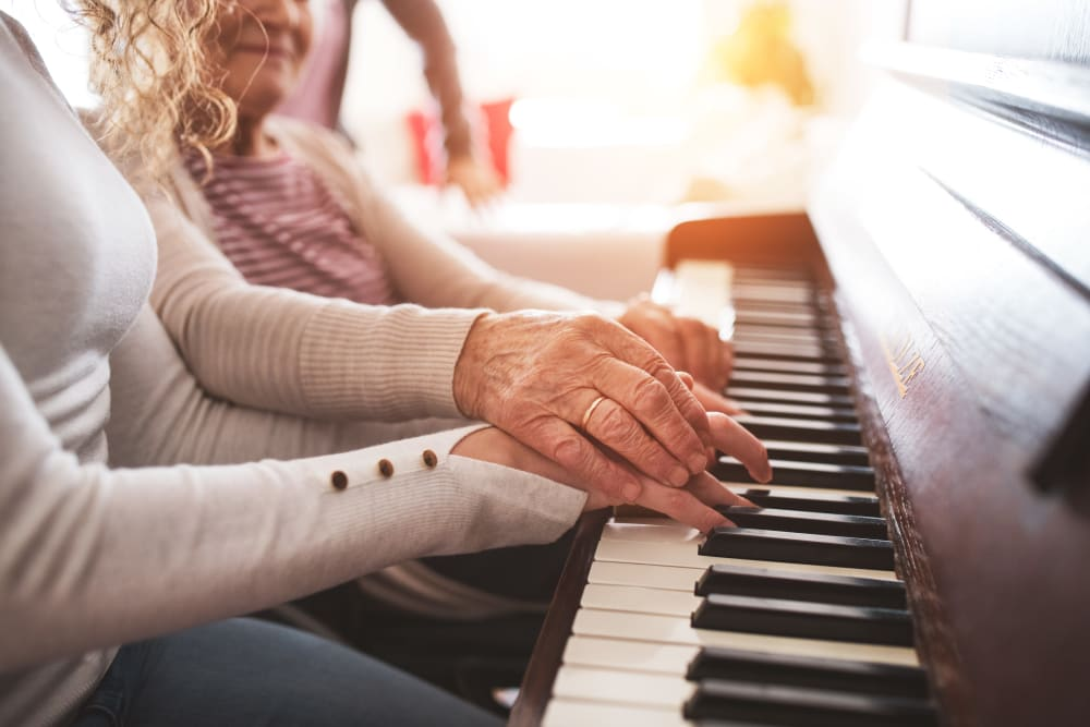 A resident plays the piano with the help of another at Arlington Place of Grundy Center in Grundy Center, Iowa