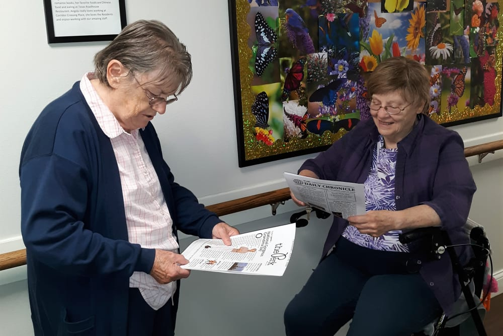 Resident friends reading the monthly news bulletin at Corridor Crossing Place in Cedar Rapids, Iowa