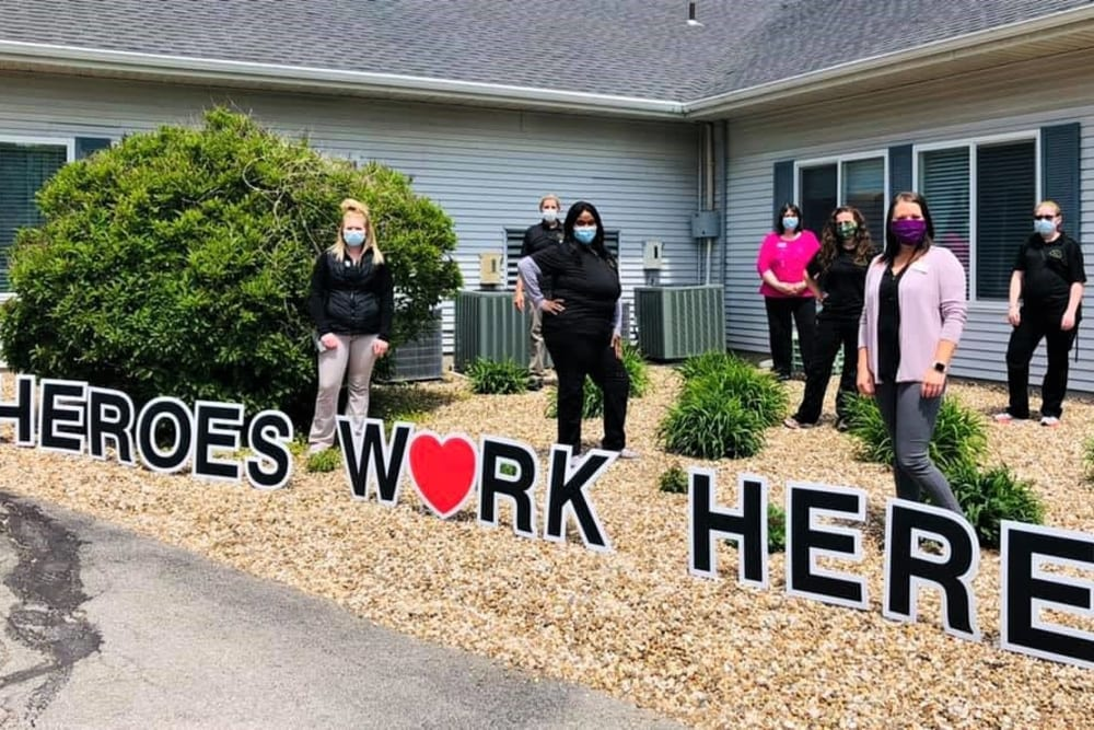 Staff pose outside building with heroes work here sign at Corridor Crossing Place in Cedar Rapids, Iowa