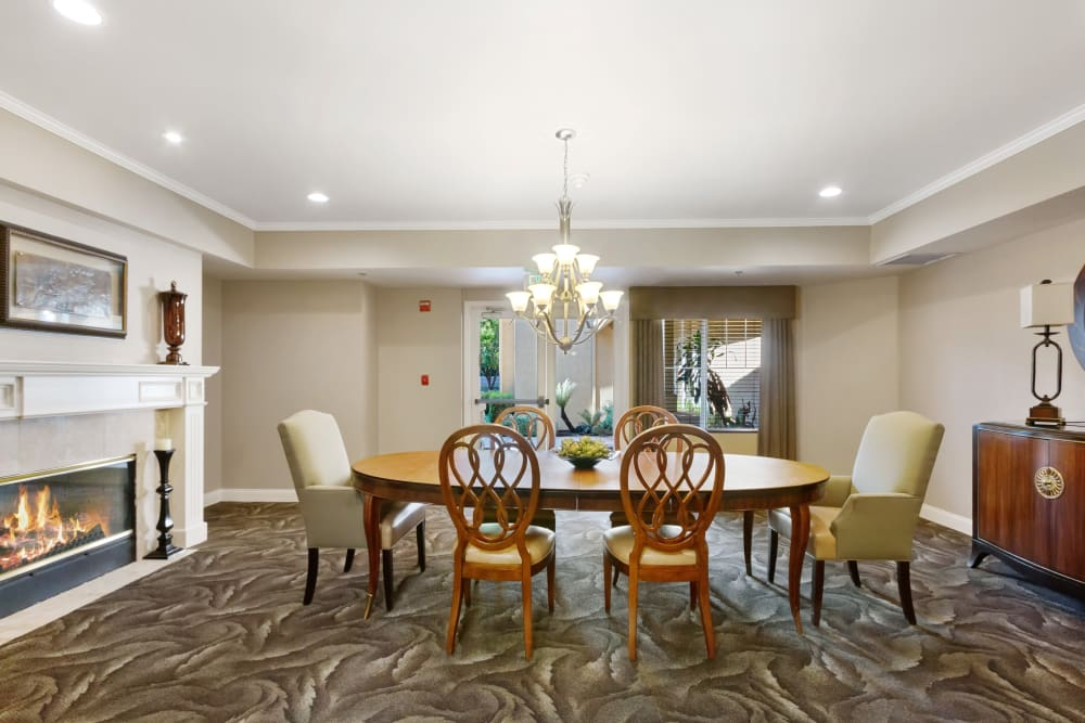 Large table with chairs and a fireplace at Claremont Place in Claremont, California