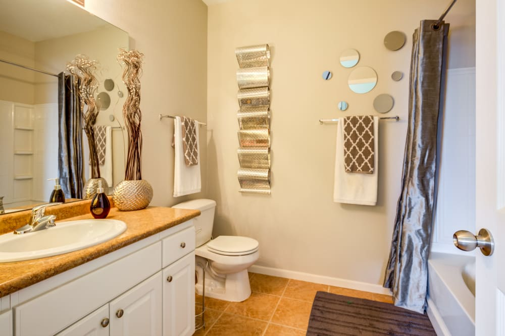 A large bathroom with a vanity mirror and an oval tub at Alvadora Apartments in Lawrence, Kansas