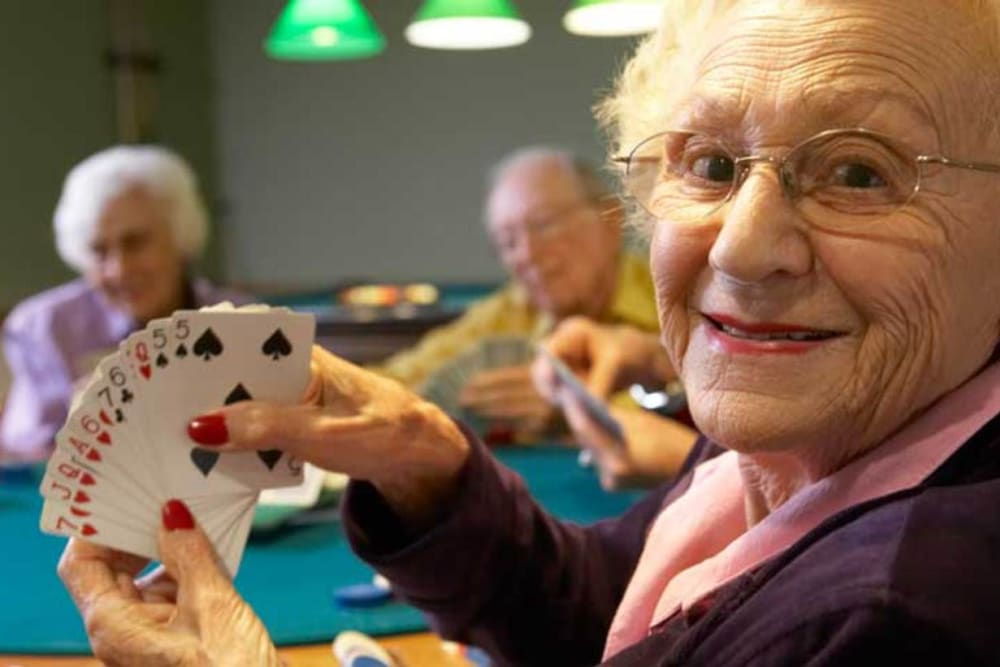 Senior woman smiling about her dealt cards at Inglenook At Brighton in Brighton, Colorado