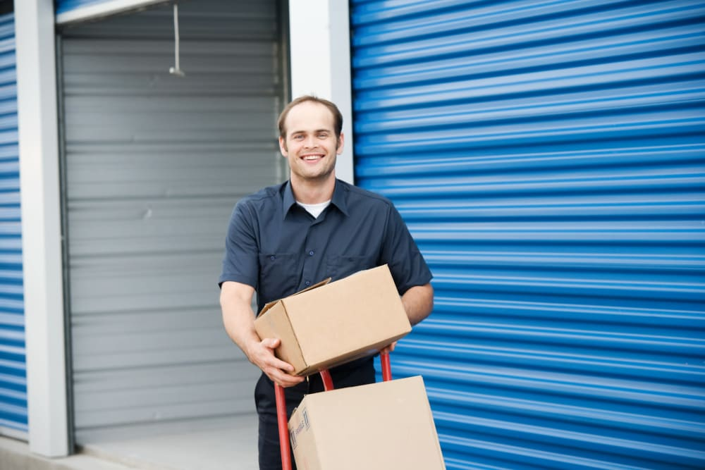 A man moving boxes out of a storage unit at StayLock Storage in Athens, Georgia
