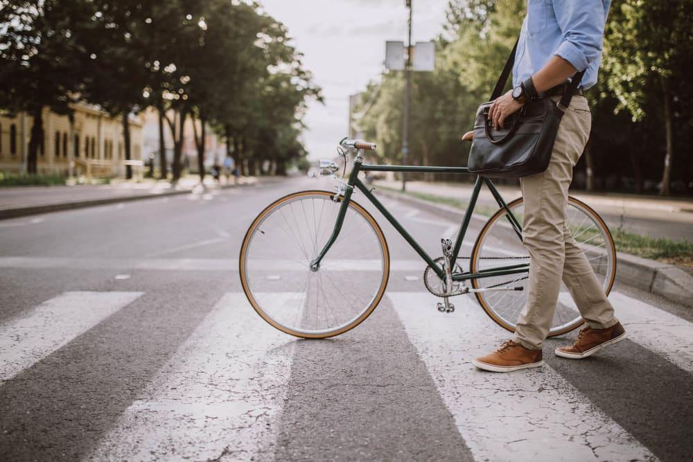 Resident walking their bike across the street near The Gage in Denver, Colorado