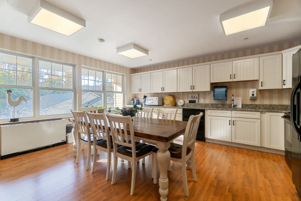 Family dining room with a long table and access to a kitchen at The Hearth at Gardenside in Branford, Connecticut