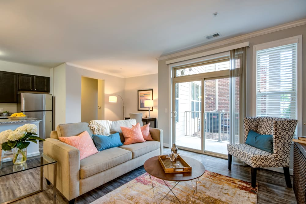 A spacious living room with wood-style flooring and a private balcony at Manassas Station Apartments in Manassas, Virginia