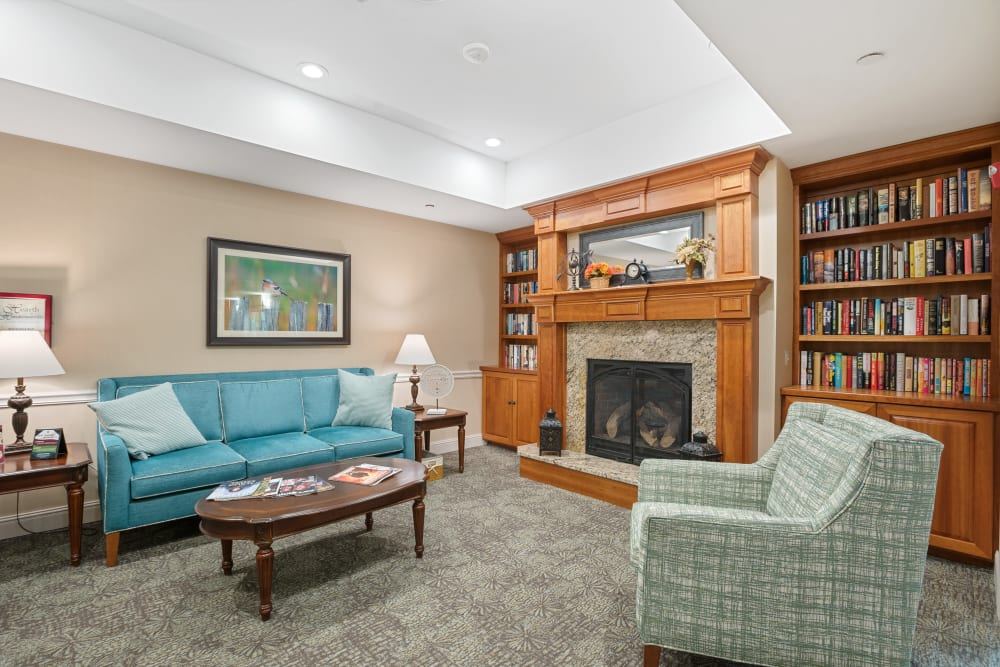 Lounge with a fireplace, full bookshelves and places to sit at The Hearth at Hendersonville in Hendersonville, Tennessee