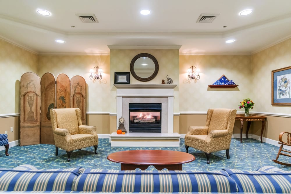 Fireplace lounge with three padded chairs, a rocking chair, and a couch at The Hearth at Southbury in Southbury, Connecticut