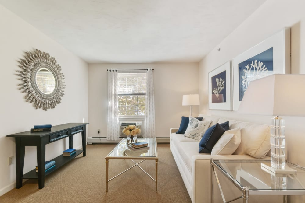 1 Bedroom senior apartment living room with a white couch and glass coffee tables at The Hearth at Tuxis Pond in Madison, Connecticut