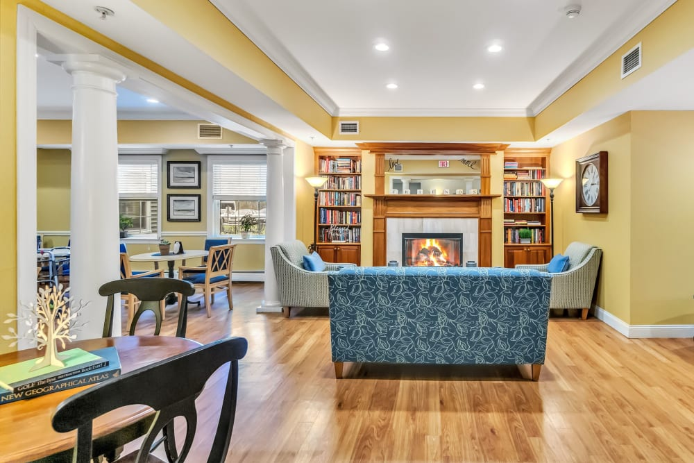 Lounge with hardwood floors, a fireplace, and a couple full bookshelves at The Hearth at Tuxis Pond in Madison, Connecticut
