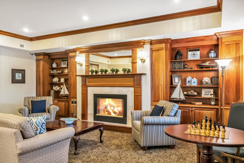 Lounge with a fireplace, several chairs, a couch, and a chess table at The Hearth at Tuxis Pond in Madison, Connecticut