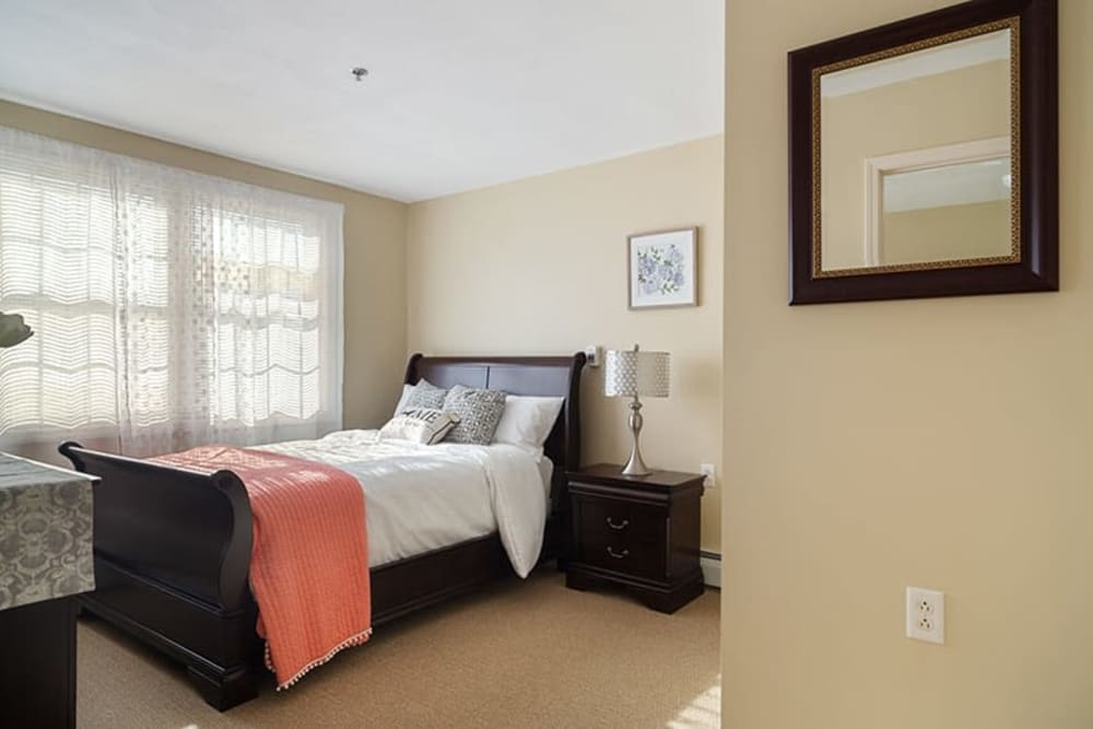 Bed next to a large covered window in an apartment at The Hearth on James in Syracuse, New York