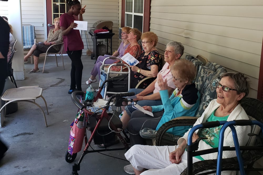 Residents enjoying social time outside on the porch at Landings of Blaine in Blaine, Minnesota