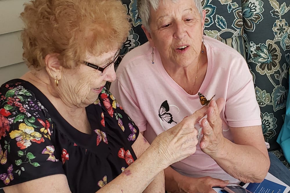 Residents handle a butterfly at Landings of Blaine in Blaine, Minnesota
