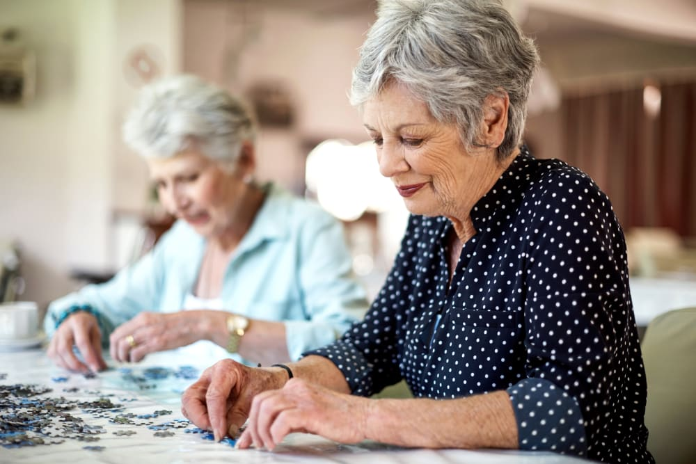 Residents putting together puzzles at Inspired Living Delray Beach in Delray Beach, Florida