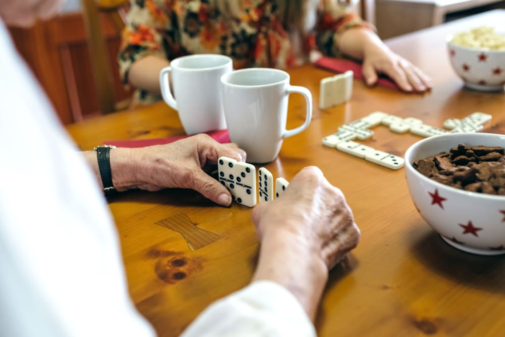 Residents playing dominoes at Inspired Living Delray Beach in Delray Beach, Florida